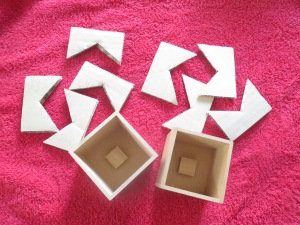 Two prototypes of the MMMM puzzle. The pieces are made from corrugated cardboard of two different thicknesses. The boxes are made from MDF and the obstacle, which is on the bottom of the box in these prototypes, is made from wood. (Photo courtesy Iwahiro)